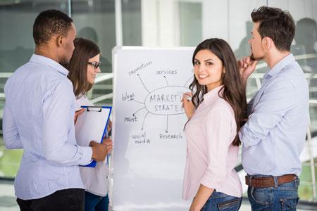 Eine junge Frau schaut in die Kamera und arbeitet zusammen im Team mit anderen Personen an einem günstigen Flipchart