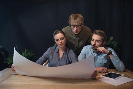Eine Gruppe von Menschen schauen auf ein großes weißes Papier. Zum transportieren braucht man ein Flipchart Köcher Transportrolle.